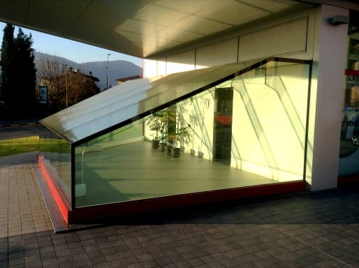 """travi in vetro brevettate sistema VTRS con geometria """"a ginocchio"""" realizzate nella vetrina espositiva di un moderno edificio commerciale a Concesio (BS)."""